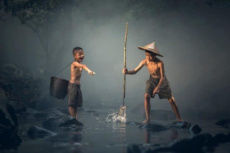 niños pescando en el río