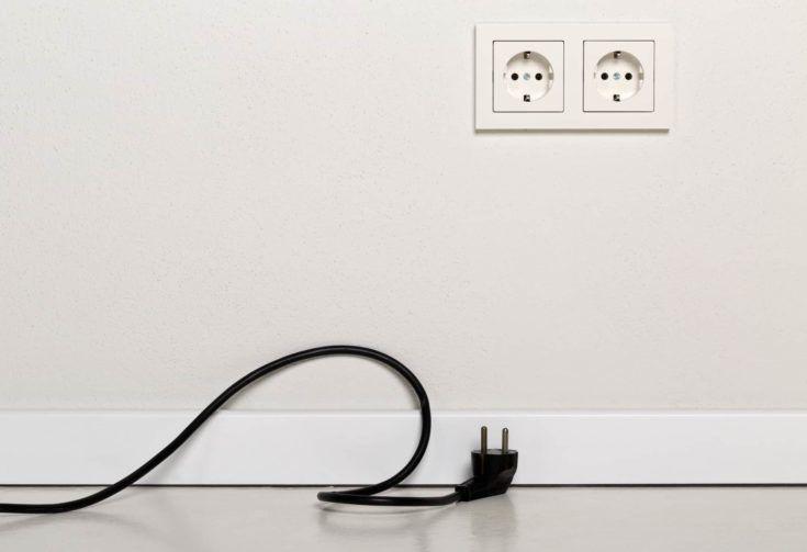 Cable de alimentación negro desenchufado con tomacorriente europeo en pared de yeso blanco con espacio de copia