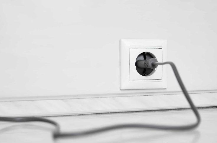 Toma eléctrica blanca y uno enchufado en el cable de alimentación sobre fondo de pared blanca
