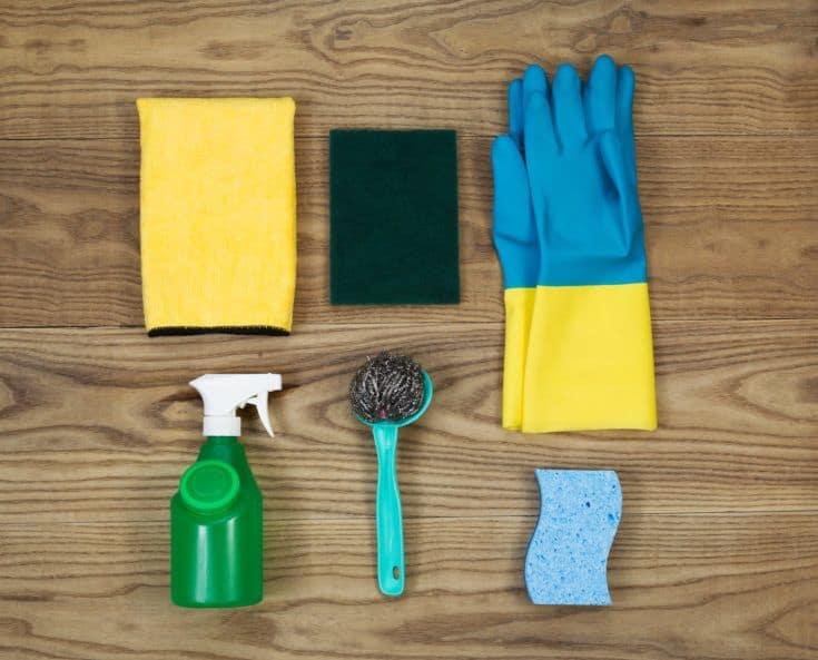 Vista aérea de los materiales de limpieza de la casa colocados sobre madera rústica.  Los artículos incluyen esponja, guantes de goma, almohadilla de acero inoxidable, botella rociadora, trapo de microfibra y almohadilla para fregar.