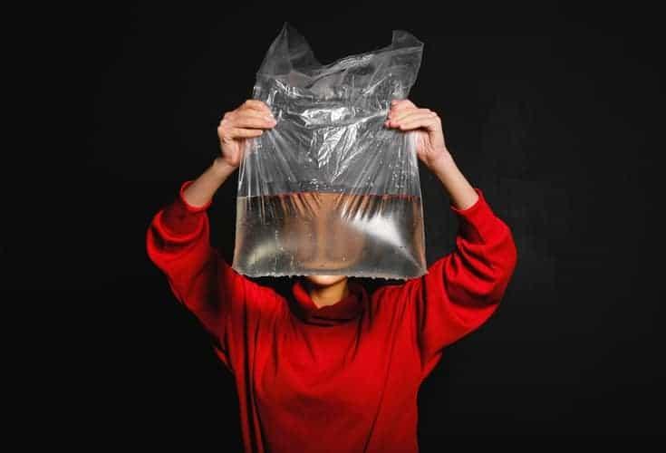 mujer sosteniendo una bolsa de plástico con agua